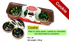 Cookie with date paste center filled and coated by cocoa and decorated by pistachio